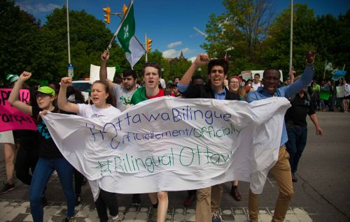 "Colour photograph of five young people, fists raised, walking briskly, holding a banner with the slogan: ""Ottawa bilingue officiellement/Officially bilingual Ottawa"". Behind them, other protesters walk down the street waving flags and carrying placards."