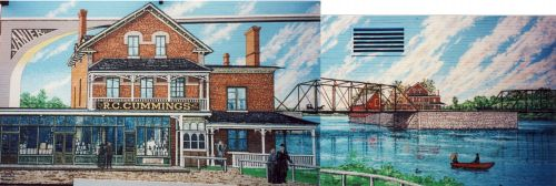 "Color photograph of a mural depicting near and far views of the ""R.C. Cummings"" commercial building in red brick. The building, located on an island in the center of a river, is reached by a metal bridge."