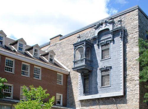 Colour photograph of an inner courtyard with a fountain in the foreground, and two buildings – one in wood, the other in stone – behind it. The metal facade of a house is fastened to the stone building, near the top of the wall.