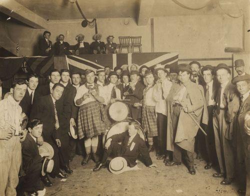 Photographie sépia d'un groupe d'une trentaine d'hommes, debout en demi-cercle, posant pour la caméra. Ils portent costumes et cravates, sauf pour deux d'entre eux, qui ont des kilts. Au centre, un homme assis sur le sol devant deux tambours. Derrière le groupe, cinq hommes sont assis sur une plateforme, devant laquelle est drapé un drapeau britannique.