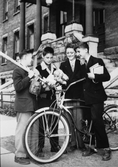 Black and white photograph of four male teens in front of a brick building. Their eyes are turned toward a baseball held  by one of the boys, who is straddling a bicycle. They are dressed in suits and ties. Three of the boys hold books. The fourth holds a baseball bat and glove.