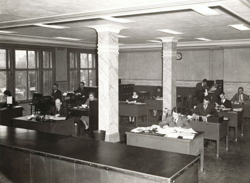 Black and white photograph of the interior of an open concept office. Seen from the front of the room, eight men and four women sit at desks, working. Large windows line one of the walls.