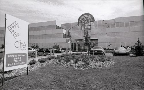 Black and white photograph of a large, three-storey building with a skylight and many windows. Cars are parked on either side of a wide entrance. A large Cité collégiale sign is positioned in the green space leading to the entrance of the building.