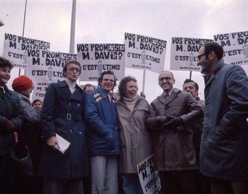 Photographie en couleur de quatre hommes et d'une femme d'âge mûr, à l'avant d'un groupe de manifestants. Ils sourient et tiennent des pancartes où il est écrit : « Vos promesses, M. Davis ? C'est l'temps. On est 600 000 ! »