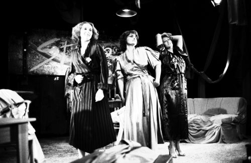 Black and white photograph of three middle-aged women in bathrobes on stage. One of the women has a hand on her hip. Another has her eyes closed and her hands behind her head. The last woman is carrying a towel over her arm. Behind them a sofa; on the wall, a banner.