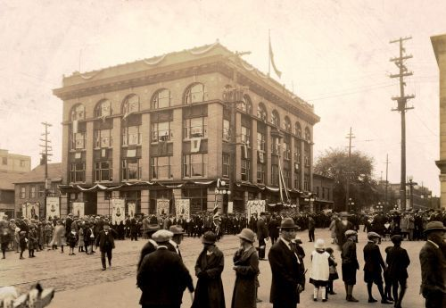Black and white photograph of a large crowd, on both sides of a city street. Men, women and children wear elegant clothes. In the background, a four-storey building, richly decorated.Many banners of the Virgin Mary and other patron saints.