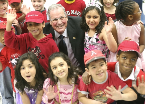 Photographie en couleur d'un homme d'un certain âge en costume-cravate. Il se tient, en souriant, au milieu d'un groupe de jeunes enfants des deux sexes et de divers groupes raciaux. Les enfants, vêtus de rouge et de rose, sourient aussi et font un signe de la main à la caméra.