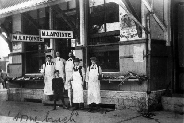 """Photographie en noir et blanc de cinq hommes en tablier blanc et d'un garçon devant une poissonnerie. Des enseignes indiquent la raison sociale de l'entreprise ainsi que sa distinction en tant que fournisseur du Gouverneur général. """"Some bunch"""" est écrit à la main en anglais, au bas de la photo."""