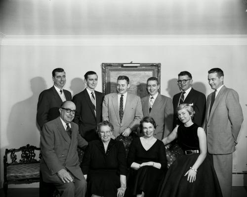 Photographie de famille, en noir et blanc. Debout à l'arrière, deux hommes d'âge mûr et quatre jeunes hommes. Assis devant, un homme et une femme plus âgés et deux jeunes femmes. Les hommes portent tous des complets, les femmes, des robes noires.