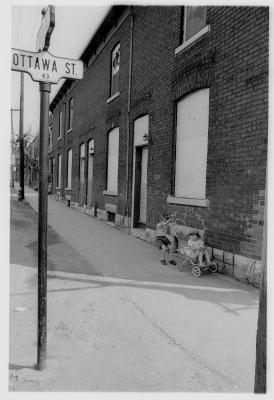 Photographie en noir et blanc d'un garçon poussant un jeune enfant dans une poussette le long d'un édifice en brique. Un panneau routier indique qu'ils sont à l'intersection de la rue Ottawa Street .