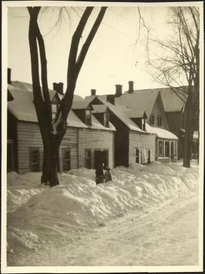 Photographie en noir et blanc d'une rue résidentielle en hiver. Les maisons en bois à deux étages ont besoin d'entretien. Un couple marche le long du trottoir enneigé.