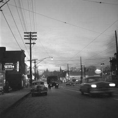 Photographie en noir et blanc d'un boulevard la nuit. Les phares des voitures et les enseignes des commerces illuminent la photographie.