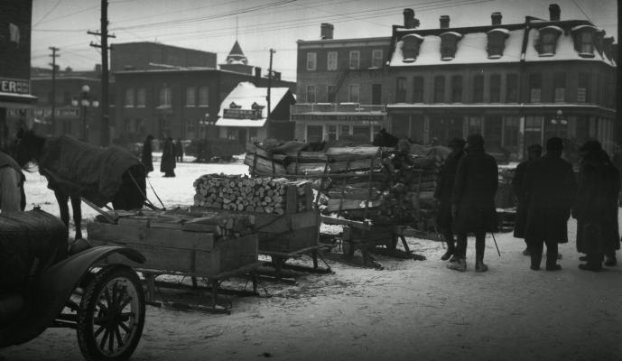 Photographie en noir en blanc d'une place de marché en hiver. Au premier plan, des traîneaux chargés de bois coupé. Plusieurs hommes vêtus de manteaux et de chapeaux devisent à côté des traîneaux.