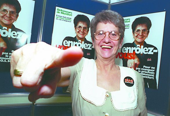 "Colour photograph of a mature woman, smiling and mimicking the gesture she herself is making on the posters behind her. On the poster she wears an S.O.S. Montfort button and points her finger at the camera. Superimposed on her chest, the slogan: ""Enrôlez-vous !'"