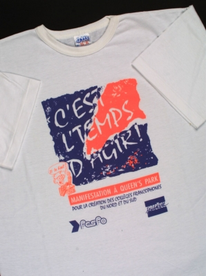 """Photograph of a white T-shirt with the words, in blue and bright orange: """"C'est l'temps d'agir !"""" (It's time to act!). The purpose of the demonstration and the logos of two organizations are also printed on the T-shirt."""
