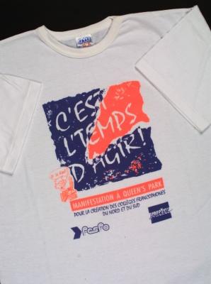 Photographie d'un tee-shirt blanc sur lequel figure l'inscription en bleu et en rouge fluo : « C'est l'temps d'agir ! ». Le but de la manifestation et les logos de deux organismes sont aussi imprimés sur le tee-shirt.