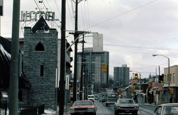 Colour photograph of a busy street with many cars. The street is lined with shops. Large buildings appear in the distance.