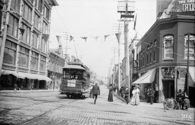 Photographie en noir et blanc d'un tramway qui circule sur un large boulevard commercial décoré de banderoles. Des gens marchent le long des trottoirs et montent dans le tramway.
