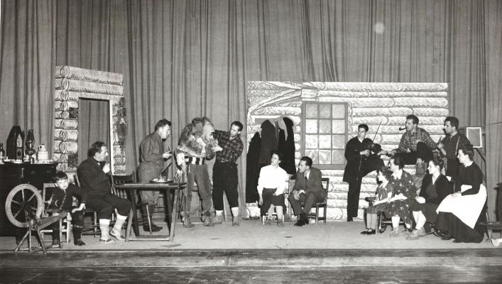 Photographie en noir et blanc d'une scène d'une pièce de théâtre. Une quinzaine d'acteurs, hommes et femmes, costumés en habitants et en voyageurs. Le décor est celui d'une maison en rondins de bois.