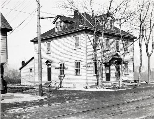 Photographie en noir et blanc d'une maison en bois à deux étages, vue de biais. Le toit est percé de deux lucarnes à fronton. La façade est bordée de grands arbres dénudés. On observe de la neige au sol.