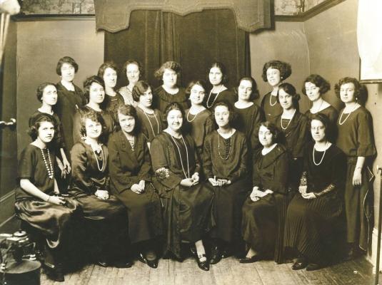 Photographie sépia d'un groupe d'une vingtaine de femmes, d'âges divers. Certaines sont assises, les autres sont debout derrière elles, en deux rangées. Toutes portent des robes noires et plusieurs portent de longs colliers de perles.