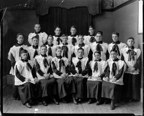 Photographie en noir et blanc, d'un groupe d'une quinzaine de jeunes garçons. Certains sont assis, les autres sont debout derrière, en deux rangées. Tous portent des soutanes et des surplis.