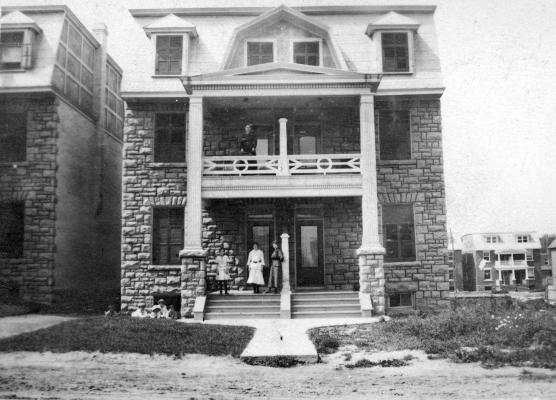 Photographie en noir et blanc. Femmes et enfants devant deux maisons attenantes en pierre à trois étages, avec balcons.