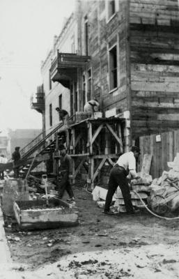Photographie monochrome sépia de six hommes construisant une maison en bois à trois étages. Le site semble rudimentaire et les travailleurs, peu préoccupés par la sécurité.