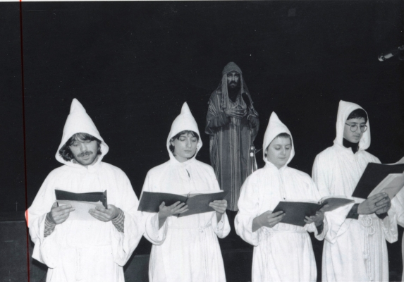 Photographie en noir et blanc de deux jeunes femmes et deux jeunes hommes, tenant des cahiers ouverts. Ils portent des tuniques, avec des capuchons. Debout derrière eux, un homme barbu en tunique rayée multicolore avec un capuchon , devant un microphone.