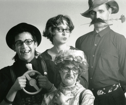 Black and white photograph of four costumed actors. One man is missing a tooth, the other wears a false mustache and holds a flower in his mouth. Between them, a women wears a cap, big glasses, and curlers; she is grimacing. The other woman is pursing her lips.