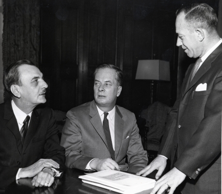 Black and white photograph of three older men in suits and ties. Two of the men sit side by side at a desk with a stack of papers in front of them. The third man stands, facing them. One man is seen in full-face view, the others in profile.