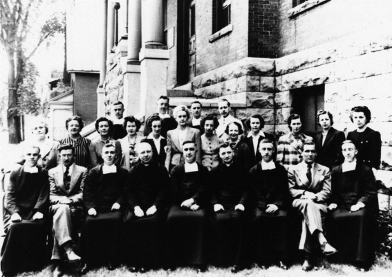 Black and white photograph of a group posing in front of a stone and brick building. The group numbers around twenty people, including mostly middle-aged men, women, and a few priests wearing cassocks. Some are sitting, with others standing behind them, in two rows.