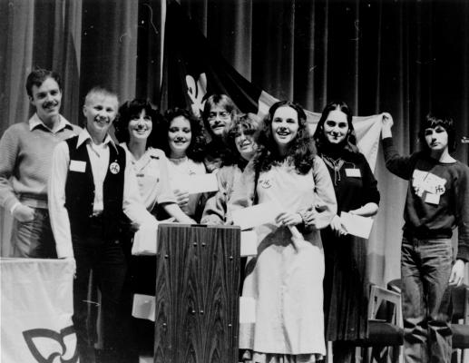Photographie en noir et blanc d'un groupe de jeunes, accompagnés de quelques adultes. Les jeunes sont regroupés autour d'un lutrin. Une jeune femme tient un document, une autre, une enveloppe. À l'arrière, un membre du groupe tend un drapeau franco-ontarien.