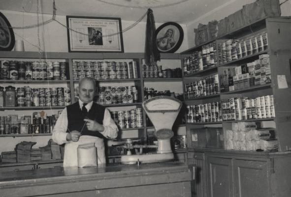 Photographie en noir et blanc d'un homme d'un certain âge, préparant un sac au comptoir d'un magasin. Derrière lui, des étagères remplies de boîtes de conserves et d'autres produits de base.