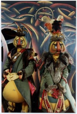 Photographie en couleur de deux personnages déguisés, lors d'une représentation théâtrale. Les comédiens portent des costumes et des masques rembourrés. Ils ont de gros nez orange, de gros yeux et de longs cils. Ils portent des chapeaux flamboyants ainsi que des vêtements garnis de fourrure. À l'arrière-plan, un décor peint avec des motifs de différentes couleurs.