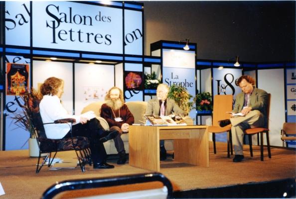 Photographie en couleur d'un groupe de trois hommes et d'une femme, sur une scène. Ils sont assis autour d'une table basse, sur laquelle sont déposés des livres. Le premier se démarque par sa longue barbe rousse. Derrière eux, un décor composé de sections où sont inscrites différentes mentions, dont « Salon des lettres ».