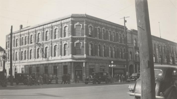 Photographie en noir et blanc d'un édifice à trois étages en brique avec beaucoup de fenêtres. L'édifice est situé dans une rue où passent de nombreux piétons et véhicules. Gravée dans la pierre, au-dessus de l'entrée principale et sur les côtés, une enseigne de la Bank of New Scotia.
