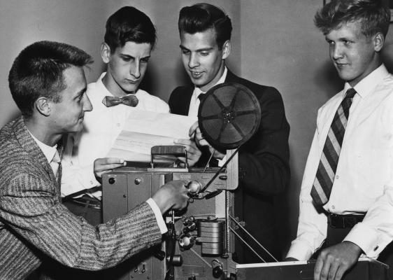 Photographie en noir et blanc de quatre adolescents autour d'un projecteur. Les deux jeunes hommes au centre de la photo lisent un document, un troisième manipule le projecteur. Ils sont tous élégamment vêtus.