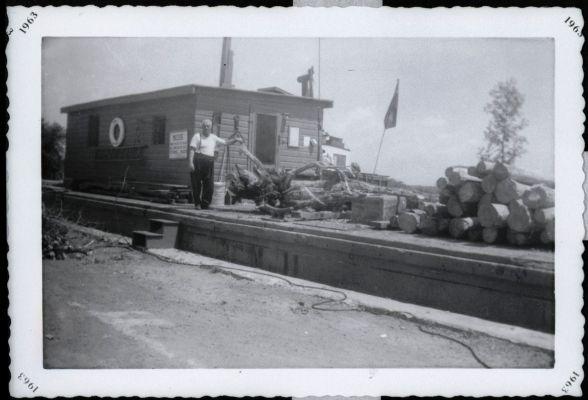 Photographie en noir et blanc d'un homme d'un certain âge, debout sur un chaland amarré. Le chaland est chargé de billes de bois.