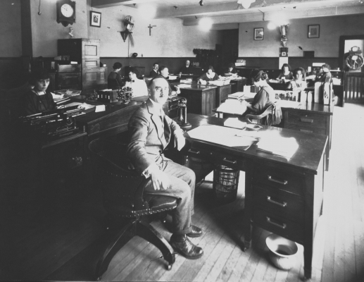 Black and white photograph of men and women working at their desks. In the foreground, a middle-aged man in a suit looks at the camera. To his left, a serious-looking young woman behind her desk.