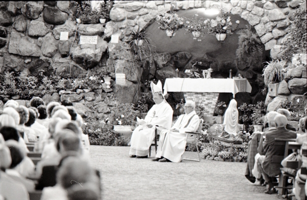 Black and white photograph of a bishop and a priest dressed in white, sitting before a cave decorated with flowers and an effigy of the Virgin. Many of the faithful, seen from behind, are seated on long benches arranged in rows.