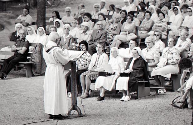 Photographie en noir et blanc d'un prêtre vu de biais, s'adressant à un auditoire, assis sur des bancs, en plein air. Il s'agit de femmes d'un certain âge pour la majorité.