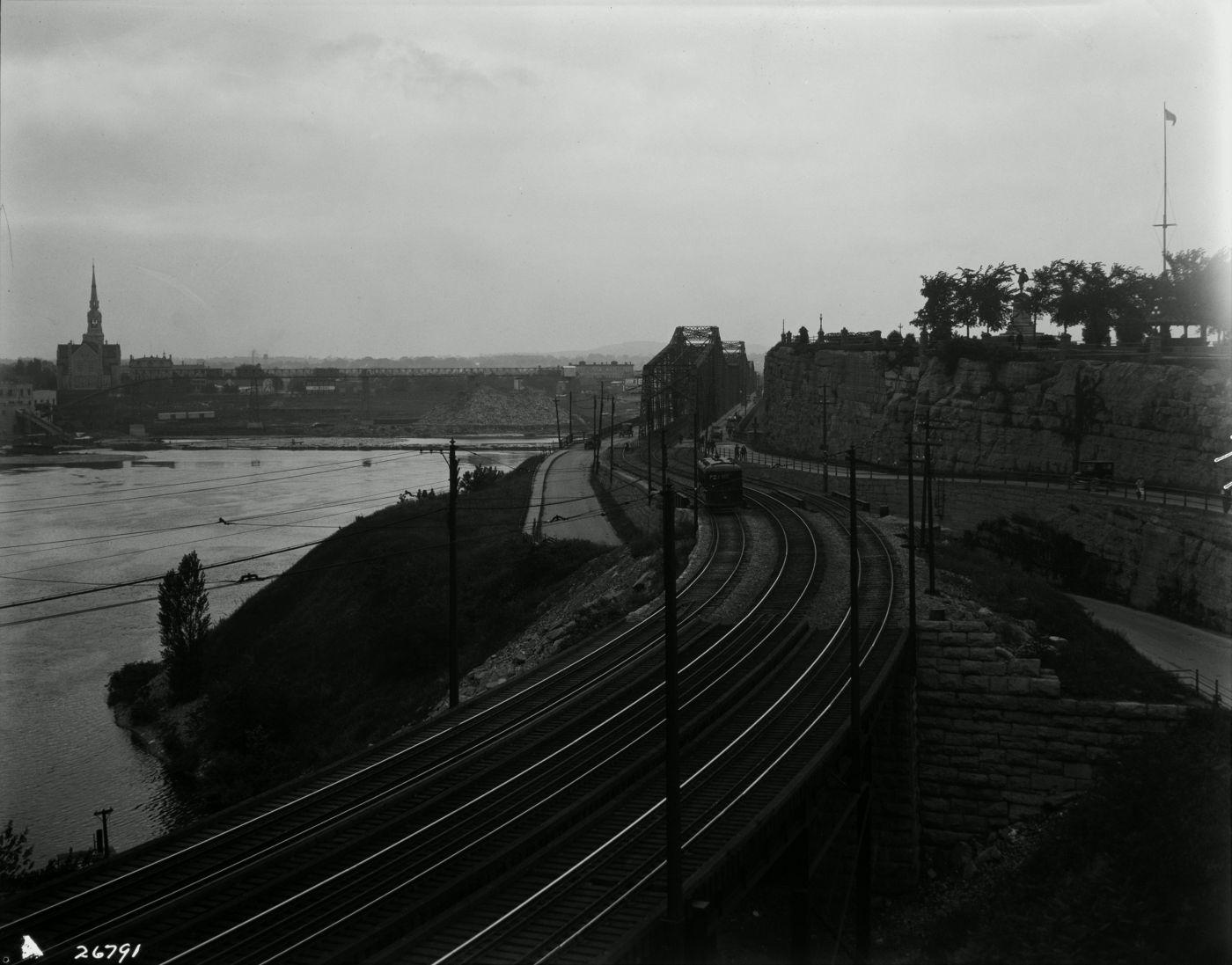 Photographie en noir et blanc d'un paysage riverain. À l'avant-plan, trois voies de chemin de fer mènent à un pont de fer. De l'autre côté du cours d'eau, un paysage industriel dominé par une église imposante.