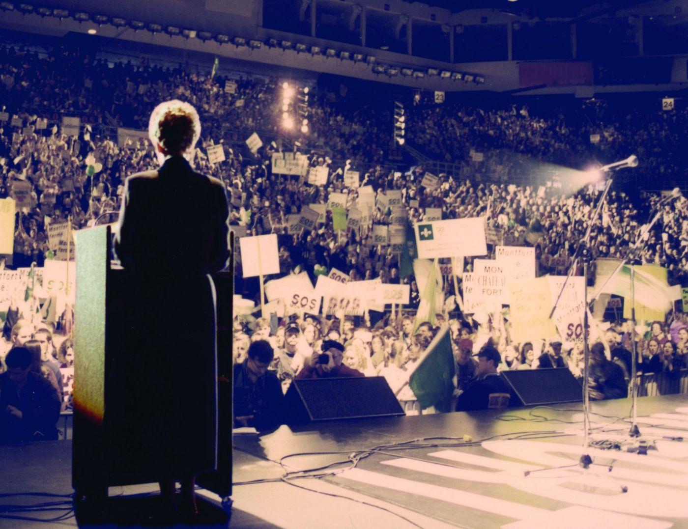 Photographie en couleur d'une femme vue de dos, debout sur une scène. Elle s'adresse au microphone à une foule dans un stade. Des gens brandissent des pancartes portant le slogan « S.O.S. Montfort ».