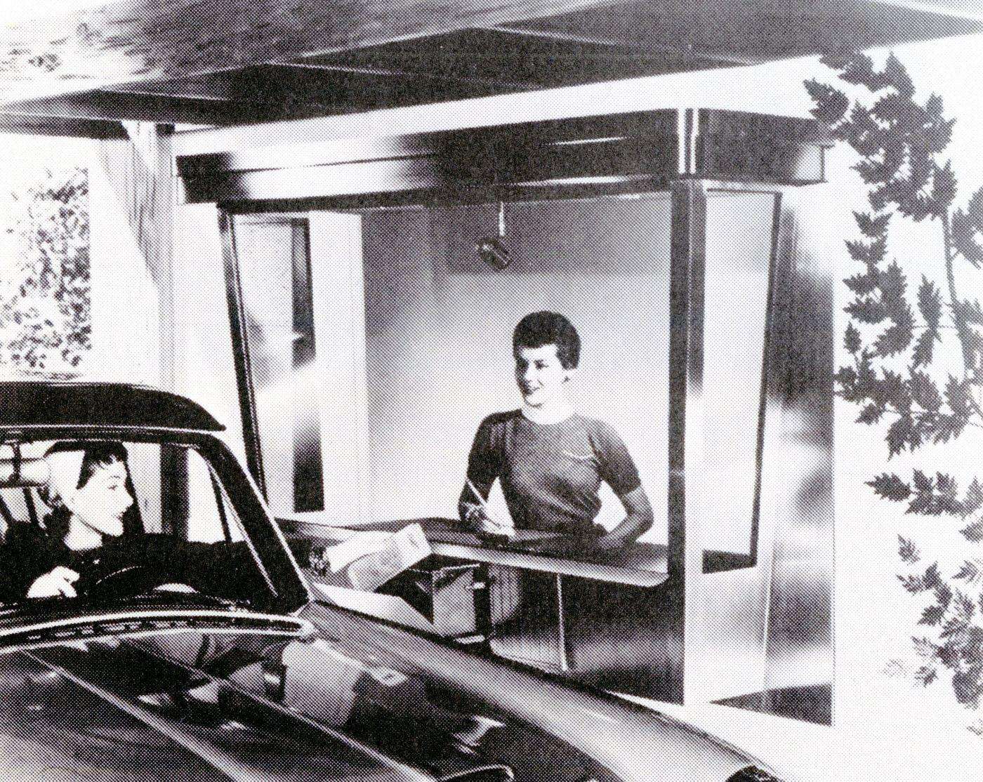 Photographie en noir et blanc d'une élégante jeune femme, passant depuis sa voiture de l'argent à une jeune femme souriante, d'allure moderne, travaillant à un comptoir de service au volant.