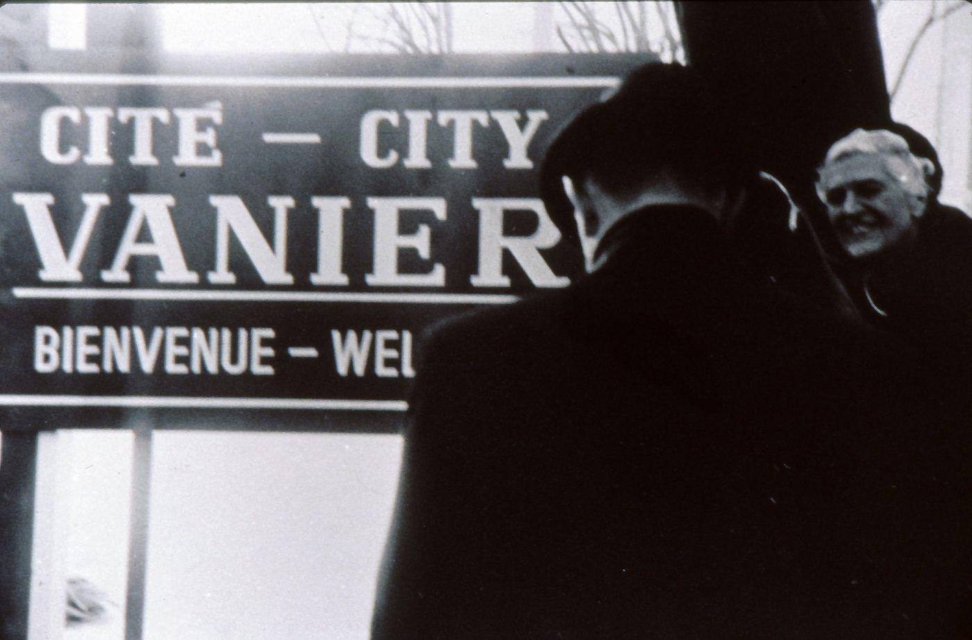 Photographie en noir et blanc d'un homme vu de dos s'approchant d'une pancarte bilingue où l'on peut lire : « Cité – City Vanier Bienvenue – Welcome ». Une femme souriante regarde l'homme.