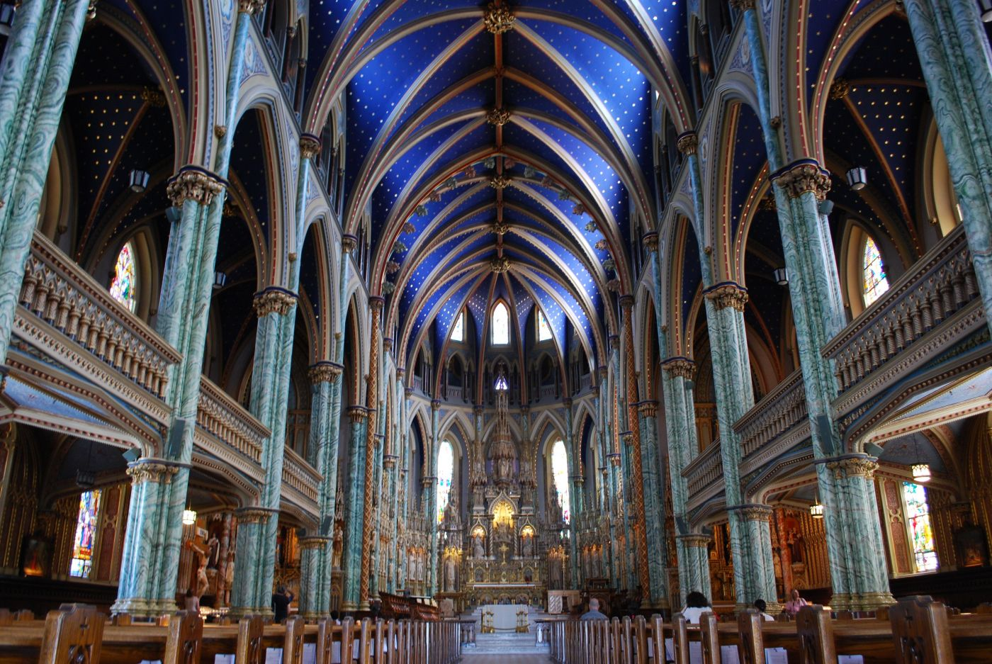 Photographie en couleur de l'intérieur d'une église de style néogothique. Des colonnes de marbre vert et blanc bordent la nef de chaque côté. Le plafond voûté est peint en bleu. Le sanctuaire est richement sculpté.