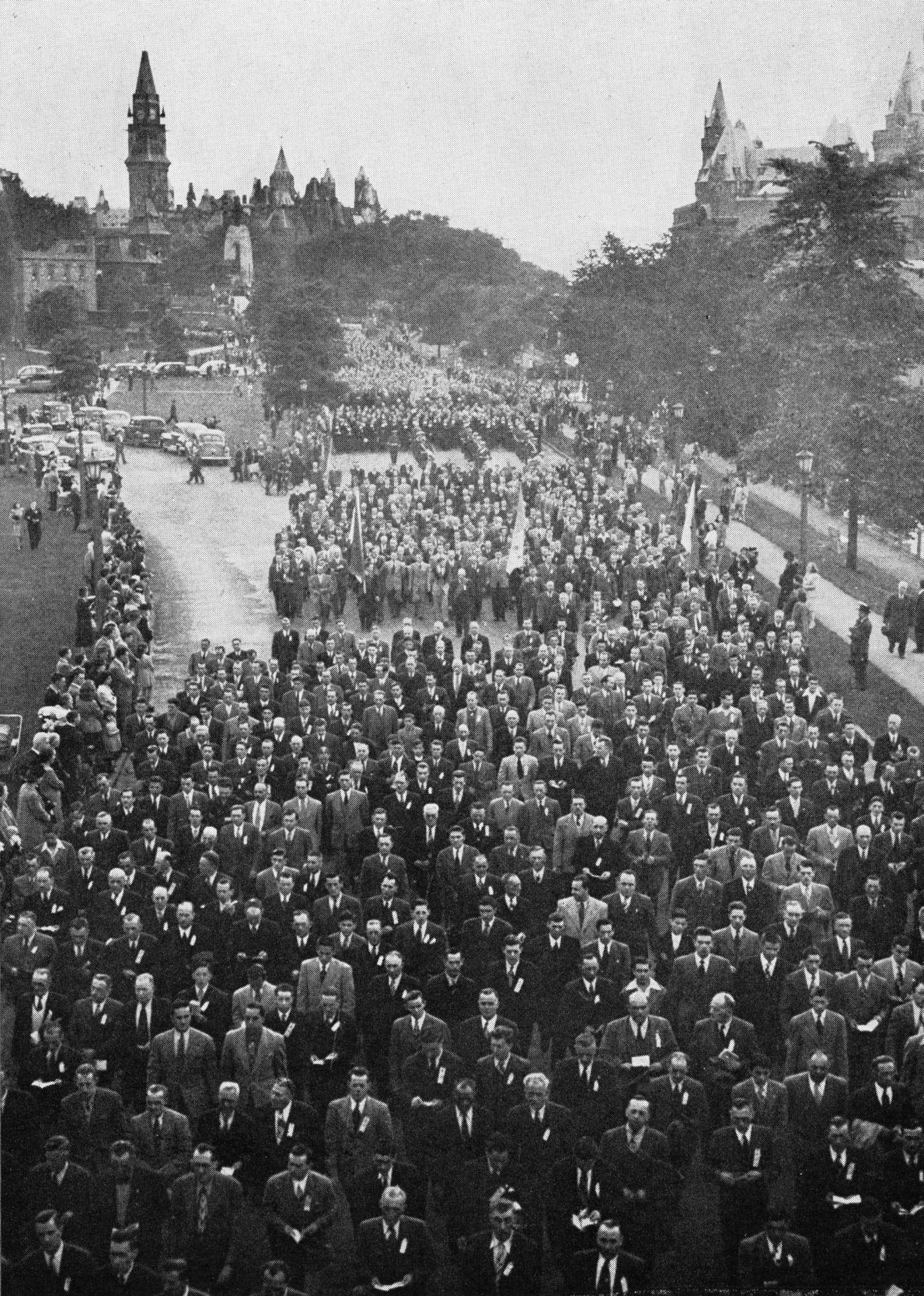 Photographie en noir et blanc d'une imposante procession. Des hommes en costumes et cravates circulent, tenant des livrets pour les uns, des drapeaux pour les autres. Des spectateurs sont massés le long du parcours. Au loin, derrière eux, le Parlement.