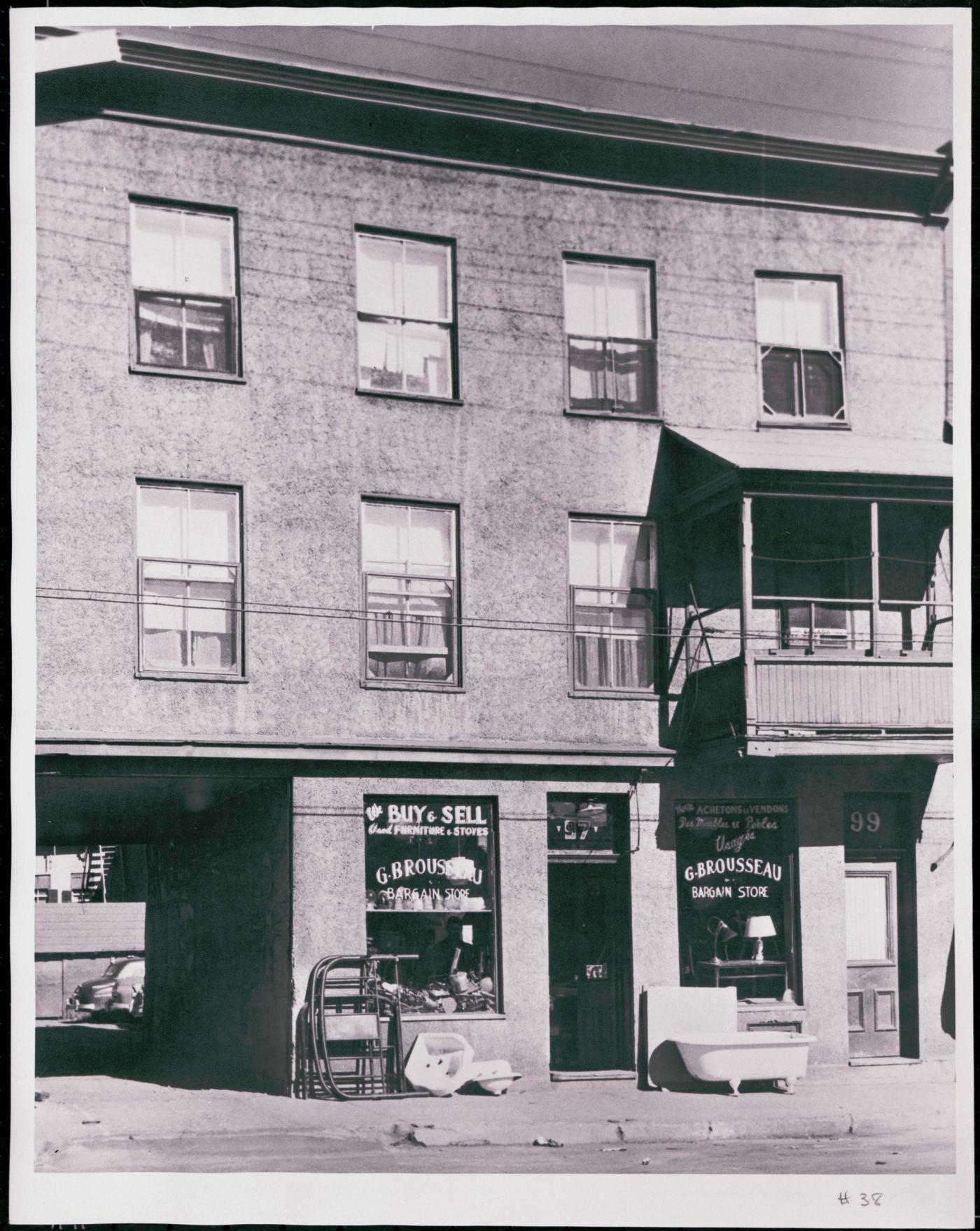 Photographie en noir et blanc d'un édifice à trois étages en stuc, avec un balcon au premier étage. Au rez-de-chaussée, un magasin d'objets usagés avec affichage bilingue à la devanture. Un passage permet d'accéder au stationnement à l'arrière de l'édifice.