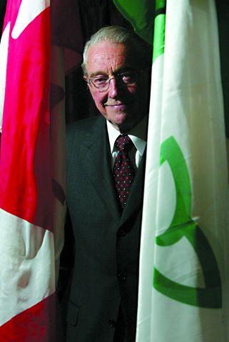 Photographie en couleur d'un homme d'un certain âge souriant. Il porte des lunettes et un costume-cravate. Il est debout entre un drapeau franco-ontarien et un drapeau canadien.
